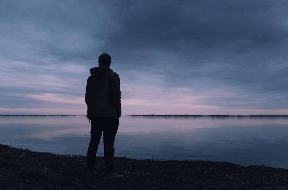 man-looking-lake-sunset-dark